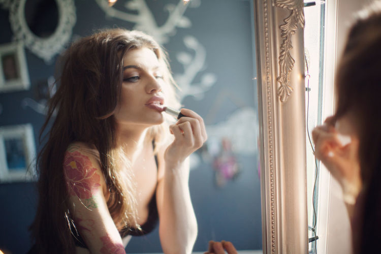 Young woman applying lipstick reflecting in mirror
