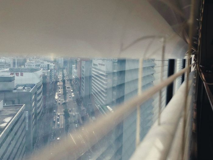 Panoramic view of city buildings seen through glass window