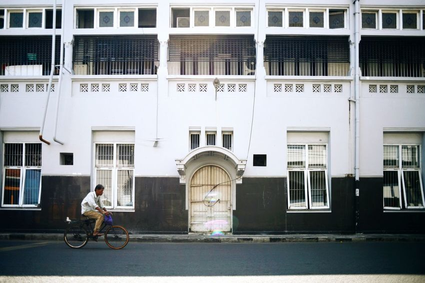 Old man riding bike in front of De Javasche Bank building. Bicycle Building Exterior Architecture Window Built Structure Politics And Government City Outdoors Day People Old Buildings Old Building  Old Architecture Surabaya INDONESIA