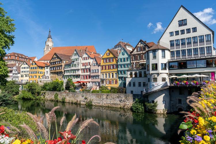 Buildings by river in town against sky