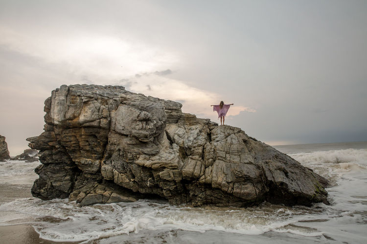 Arms Raised Beauty In Nature Freedom Full Length Human Arm Land Leisure Activity Lifestyles Nature One Person Outdoors Real People Rock Rock - Object Rock Formation Scenics - Nature Sea Sky Solid Standing Water