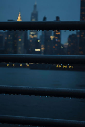 Close-up of illuminated railing by building in city
