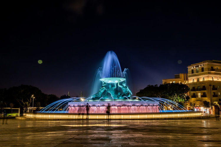 Illuminated fountain in city against sky at night