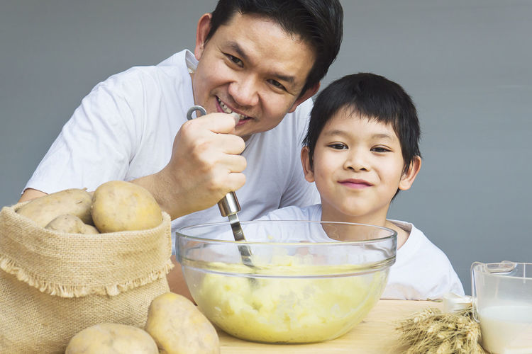 Portrait of father and son preparing food on table at home