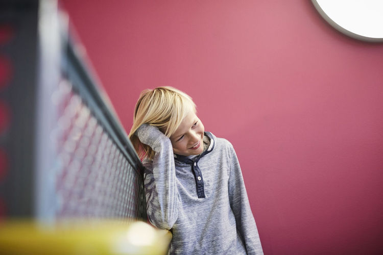 Boy looking at camera while standing against wall