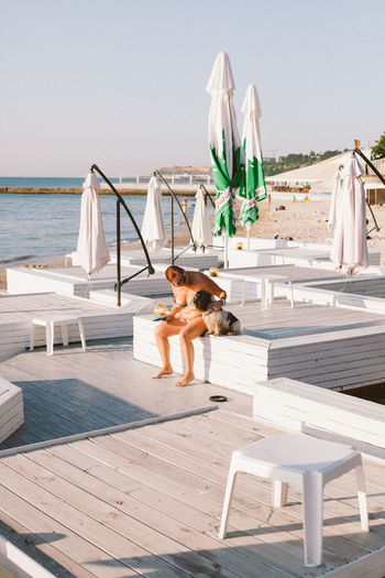 Dog sitting on chair by sea against sky
