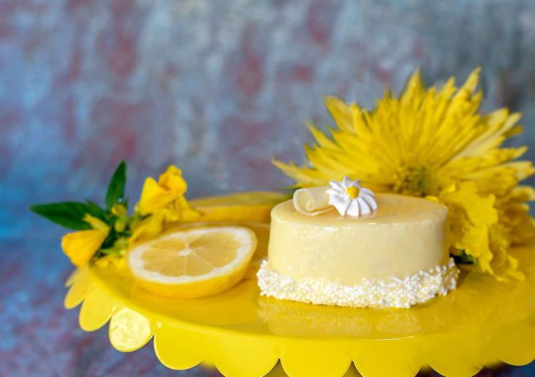 lemon glazed cake with fruit garnish and bright yellow flower