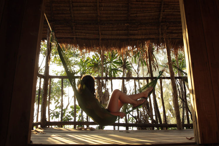 Side view of woman sitting on hammock