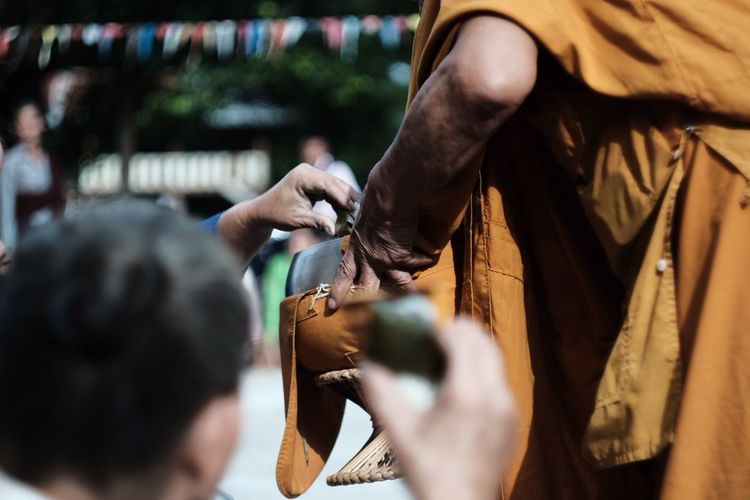 Midsection of monk serving food outdoors