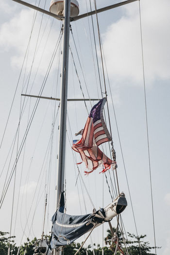 Low Angle View Of Torn American Flag On Boat Against Sky