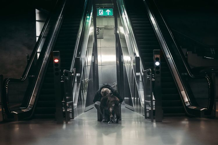 Woman with dog by escalator