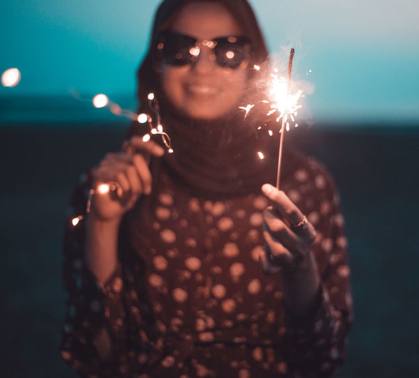 Young Woman With Illuminated Sparklers Standing At Beach During Dusk