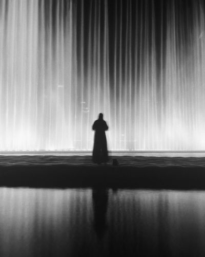 An Emirati lady watches the Dubai Fountain Blackandwhite Photography One Person Real People Silhouette Water Standing Lifestyles The Street Photographer - 2018 EyeEm Awards