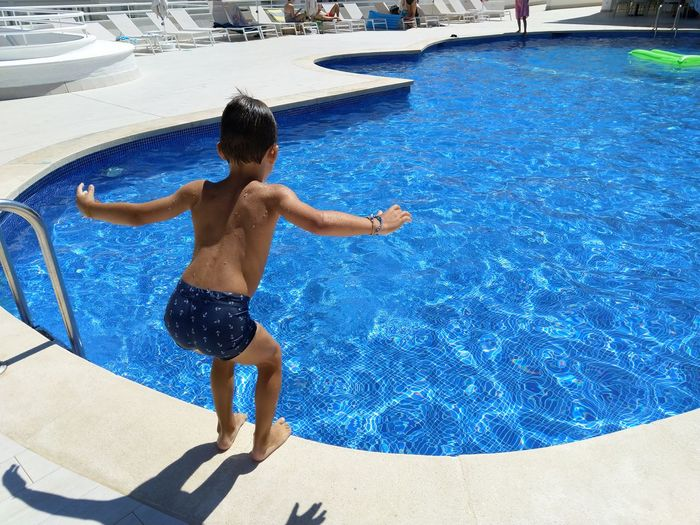 Full length of shirtless boy jumping in swimming pool