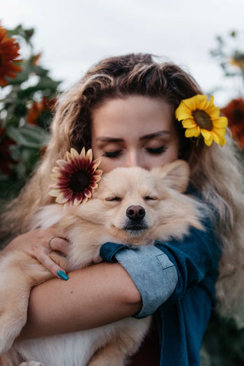 Midsection of woman holding dog at flower