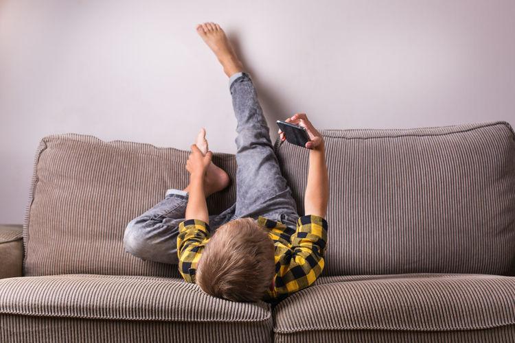 Boy using phone while lying down on sofa