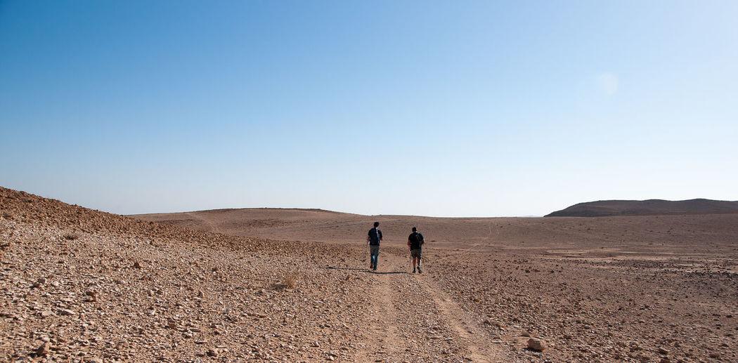 People on arid landscape against sky