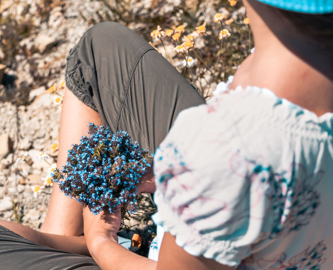 High angle view of woman holding flowers while sitting outdoors