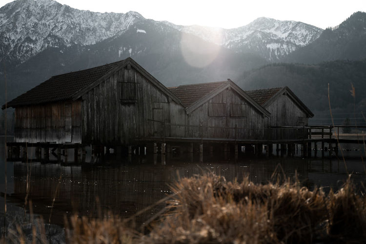 Stilt houses over lake against mountains