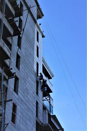 Painterly RISK Architecture Blue Building Exterior Built Structure Cable Clear Sky Connection Day Low Angle View Outdoors Sky Technology Workers At Work Painter Risky Business Risk Work EyeEmNewHere