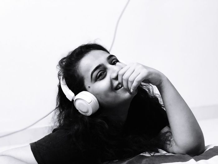 Portrait Of Happy Young Woman Listening Music Through Headphones While Lying On Bed At Home