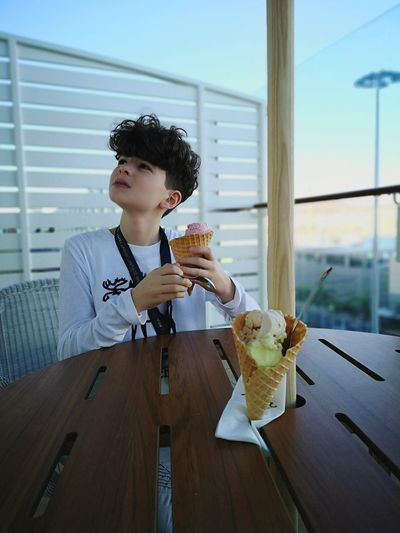 Boy holding ice cream while sitting at table