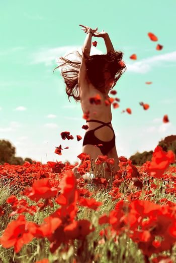 Topless Woman With Arms Raised Standing On Poppy Field Against Sky