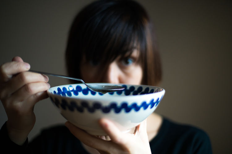Portrait of woman holding dish at home