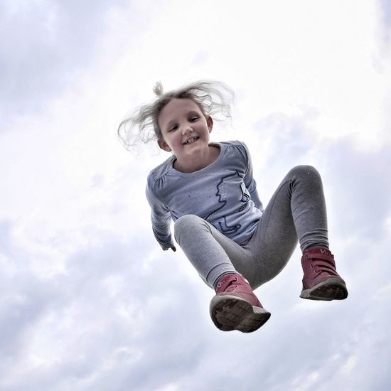Low angle view of smiling girl jumping against sky
