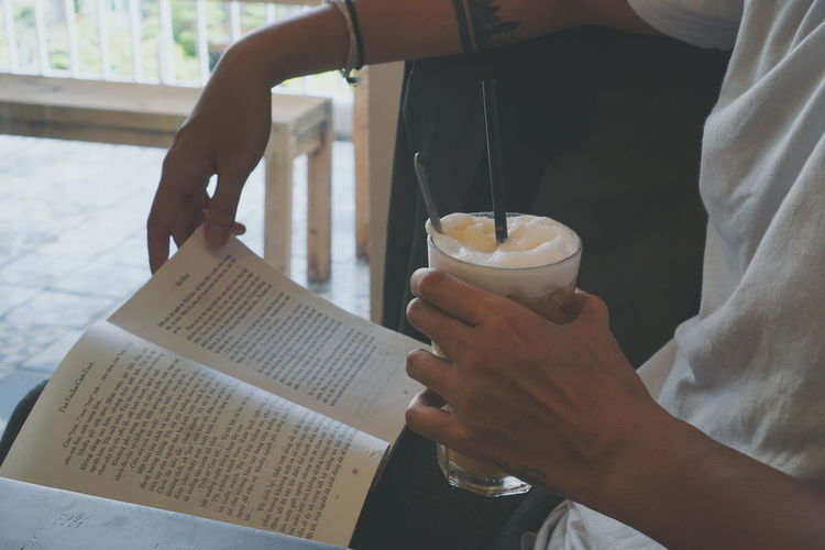 Midsection of man reading book while holding drink