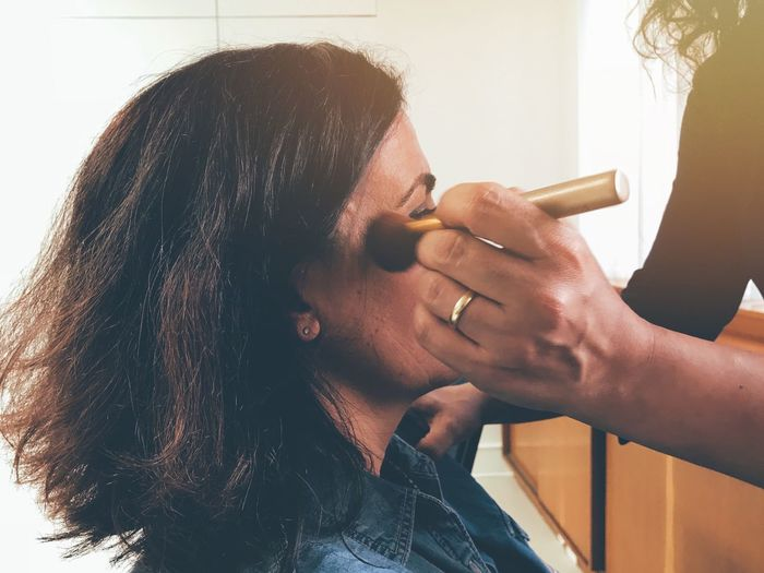 Cropped Hand Of Person Applying Make-Up On Woman Face