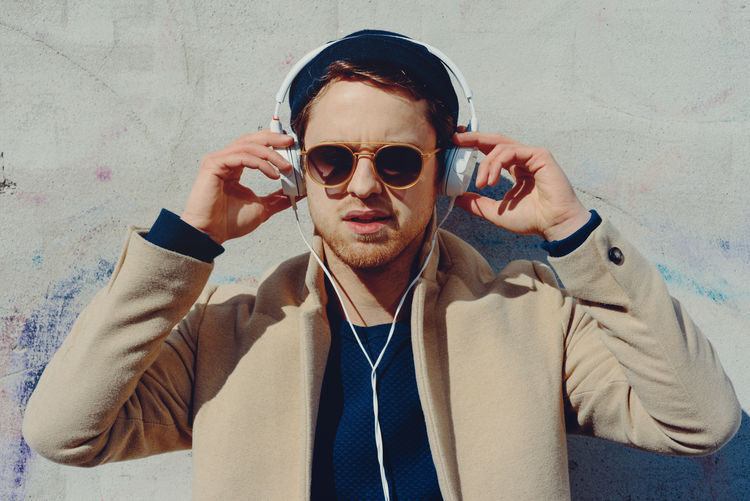 Young men with earphones Authentic Moments Bright Fashion Hands Headphones Leipzig Listening To Music Music Sunlight Wall Germany Male Mensfashion Menstyle Outdoors Situation Sunglasses White Young Adult
