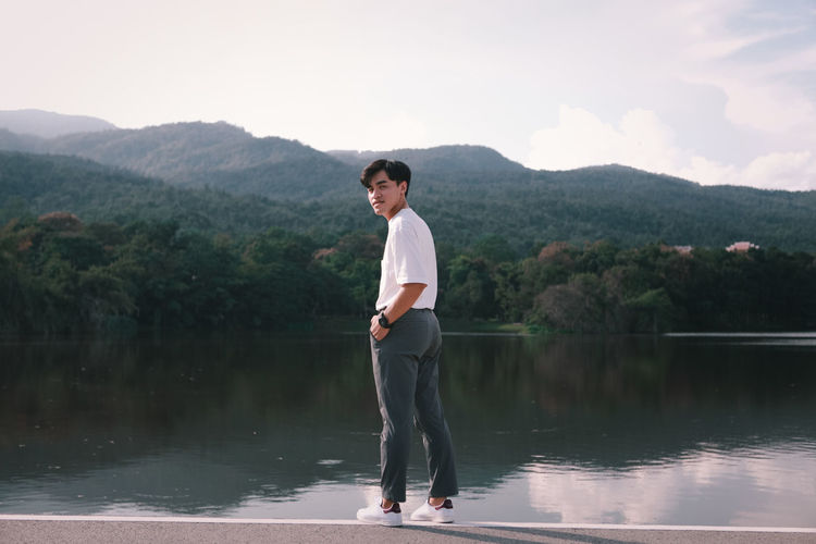 Young man standing on lake against mountains