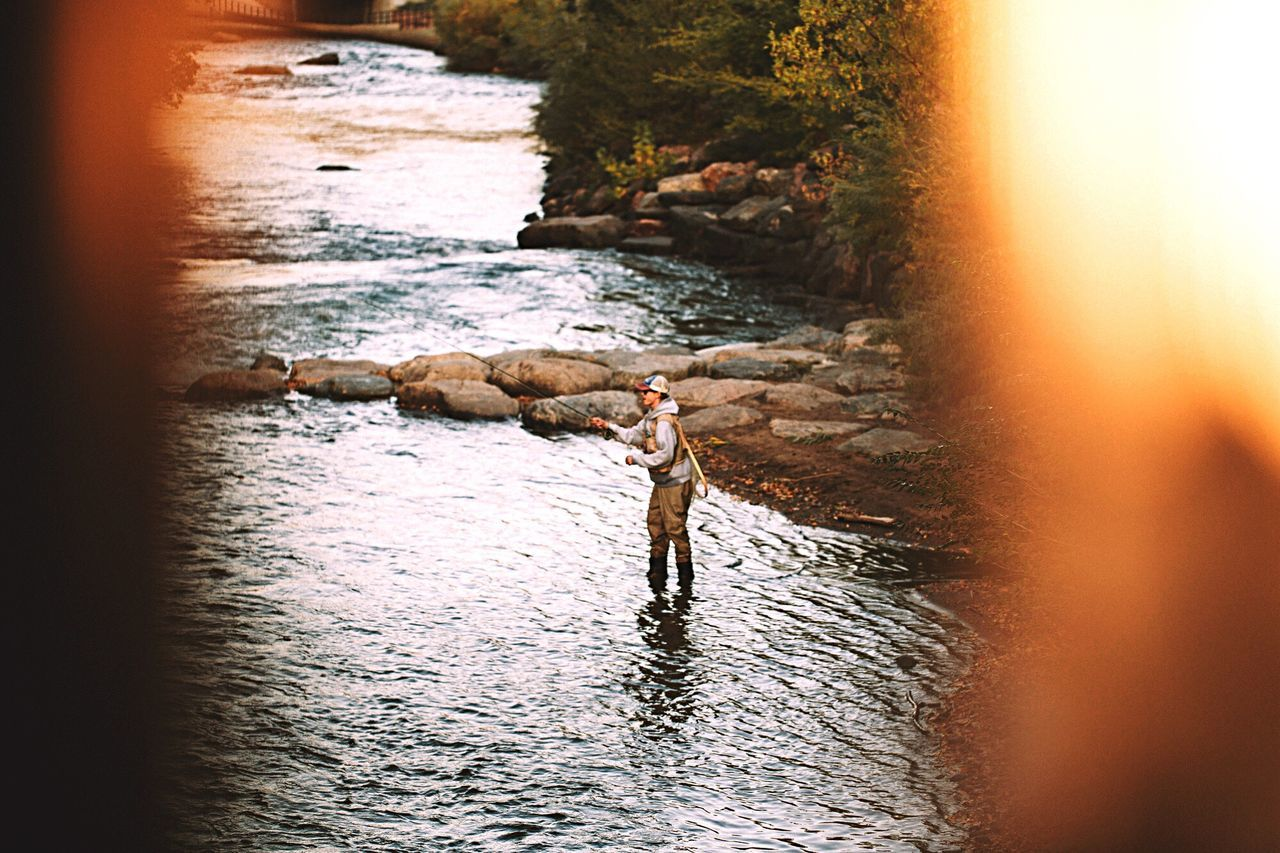 MAN STANDING BY RIVER AGAINST SKY