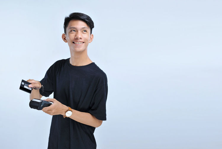Portrait of smiling young man holding camera