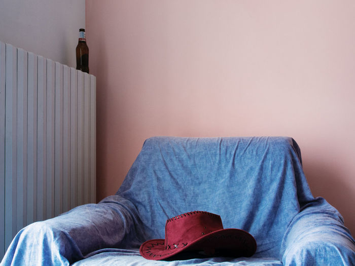 Close-Up Of A Hat On Armchair Against The Wall