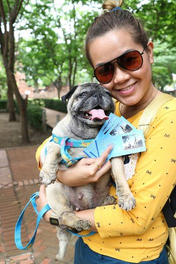 Portrait of woman holding pug