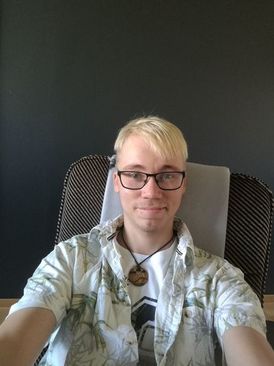 Portrait Of Young Man Wearing Eyeglasses While Sitting On Chair At Home