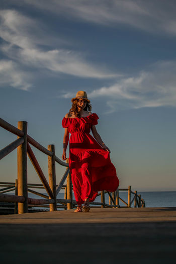Woman standing on railing by sea against sky