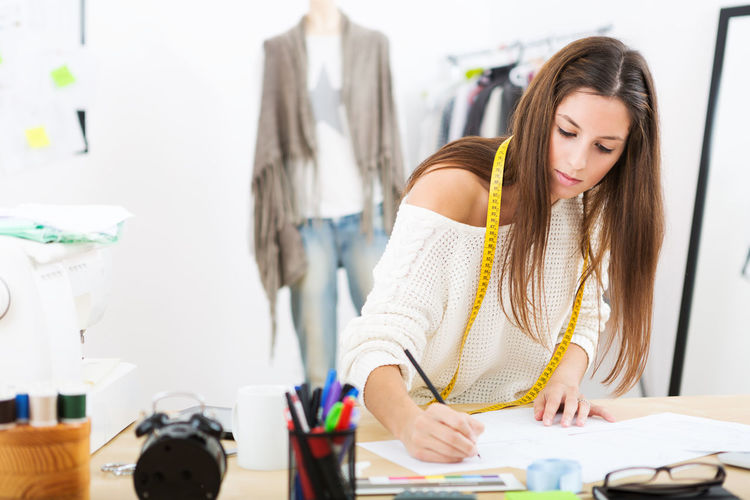 Young fashion designer working hard in her office. Office Working Adult Adults Only Blond Hair Clothes Concentration Day Design Professional Designer  Fashion Designer Holding Indoors  Long Hair Looking Down One Person One Young Woman Only People Real People Standing Table Working Young Adult Young Women