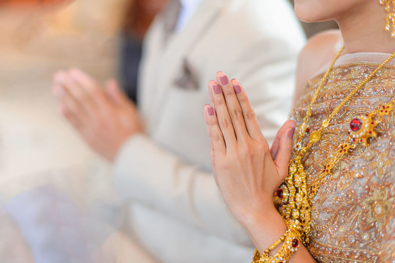 Midsection of woman holding hands against blurred background