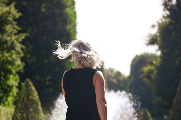 Rear view of woman with tousled hair standing against trees