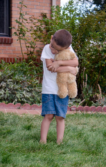 friendships come in all shapes and sizes and stuffings! this young man loves his favorite stuffed teddy bear Imagination Love Stuffed Toy Youth Boy Child Childhood Day Elementary Age Friendship Full Length Grass Hispanic Outdoors Playing Prete Real People Standing Teddy Bear