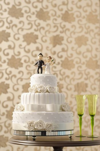 Close-up of wedding cake on table against wall