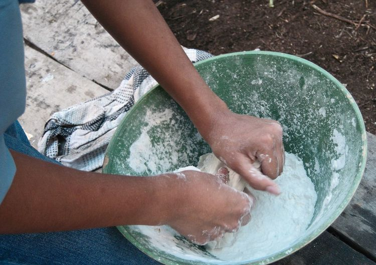 Midsection of person kneading dough while sitting on bench