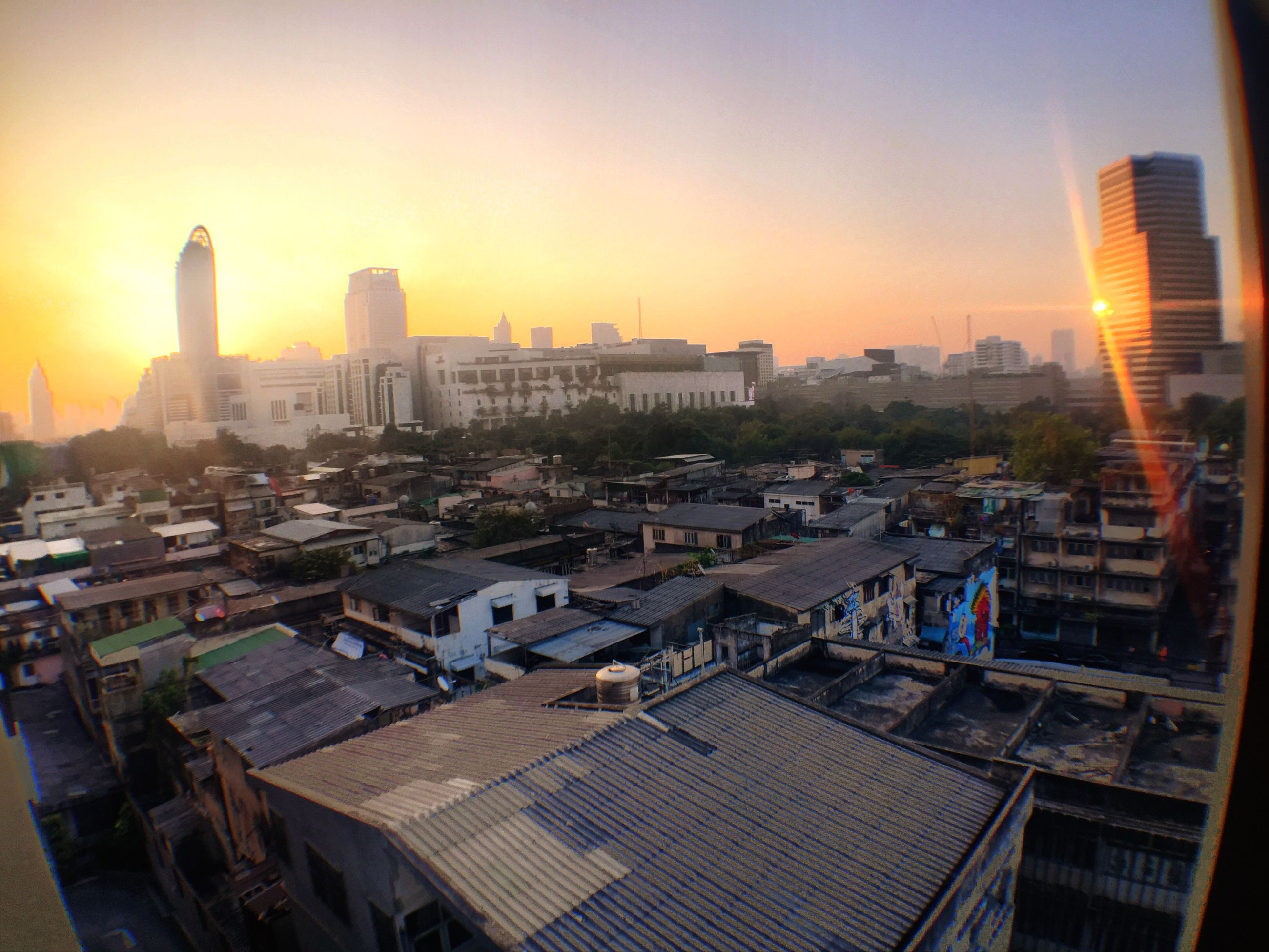 building exterior, architecture, built structure, city, cityscape, sunset, skyscraper, residential district, high angle view, residential building, crowded, sun, city life, residential structure, tall - high, tower, office building, sky, sunlight, modern