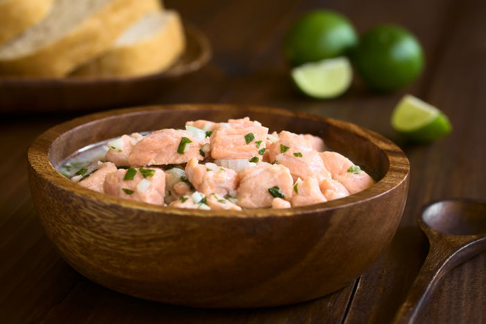 Chilean salmon ceviche prepared with onion, garlic, fresh coriander, salt and lemon juice, photographed with natural light (Selective Focus, Focus on the salmon pieces on the top of the ceviche) Breakfast Chile Chilean  Garlic Meal Raw Snack Appetizer Cebiche Ceviche Chilean Food Cilantro Coriander Fish Food Food And Drink Fresh Lemon Lemon Juice Onion Raw Food Refreshing Salmon Seafood Sour