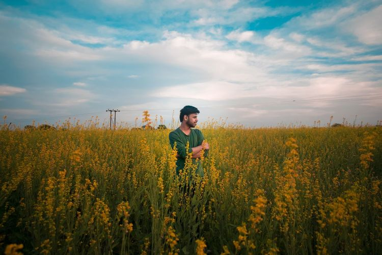 Thoughtful man standing at rape field against cloudy sky
