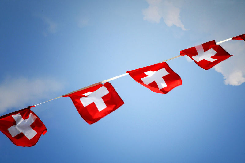 Low angle view of swiss flags hanging against sky