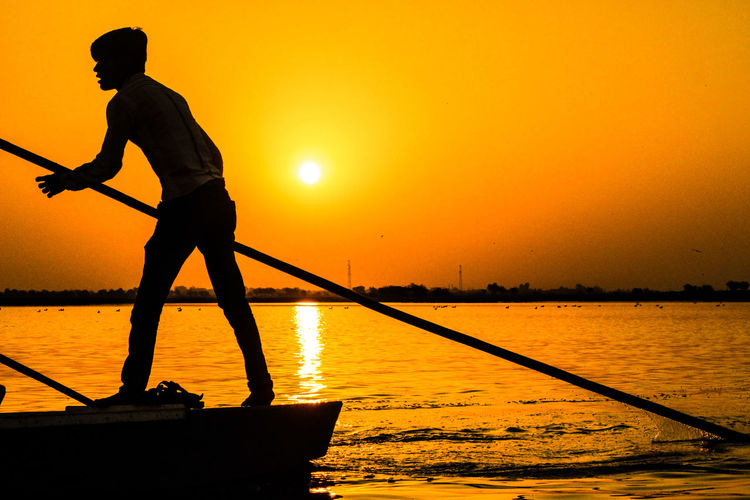 EyeEm Selects Sunset Silhouette Standing Full Length Water One Man Only Only Men Adults Only One Person Outdoors Adult Holding Men People Sea Occupation Nature Maintenance Engineer Sky Young Adult